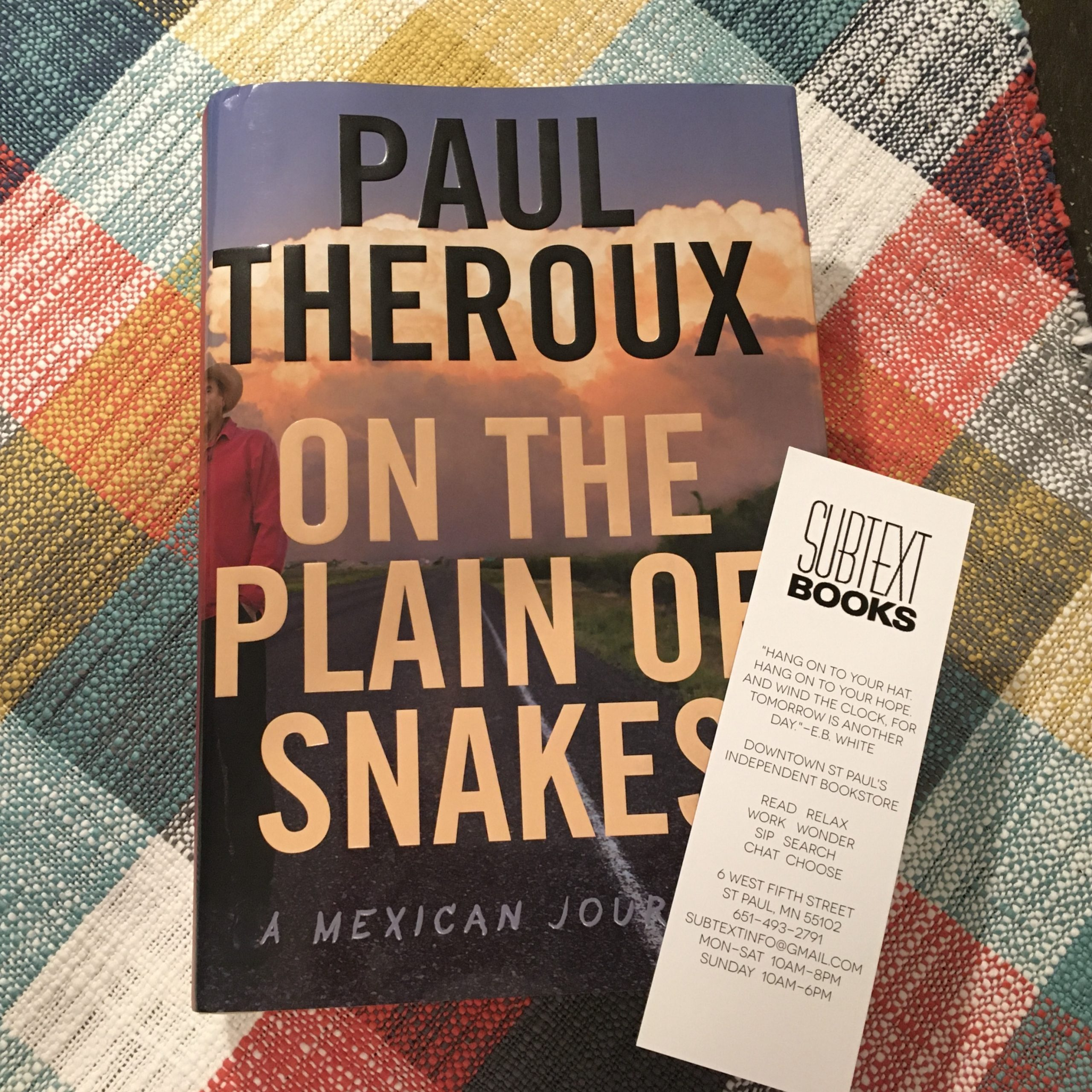 On the Plain of Snakes book by Paul Theroux and a Subtext Books bookmark on a table